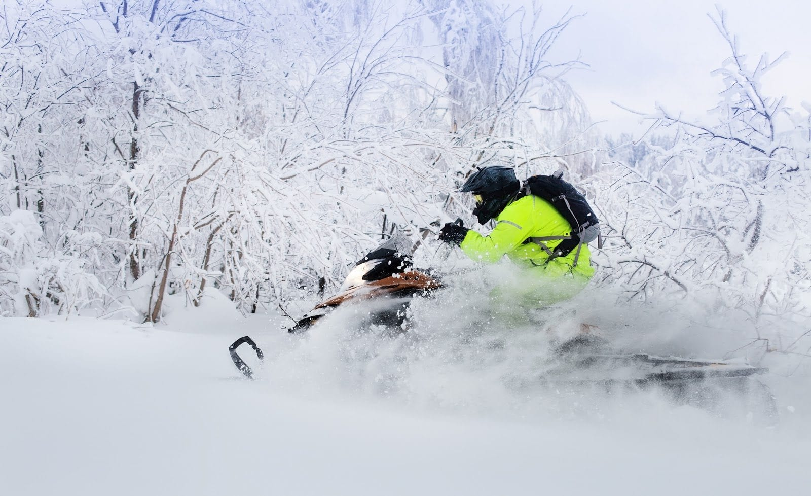 Snowmobile kicking up drifts of snow.