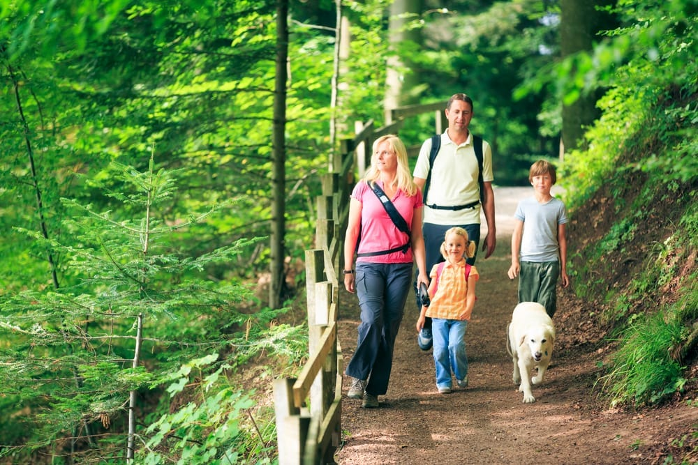 Family with a dog walking along a trail.