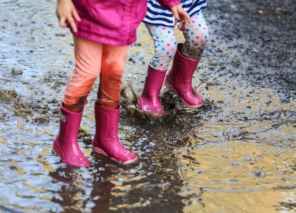 Children splashing in mud and rain.