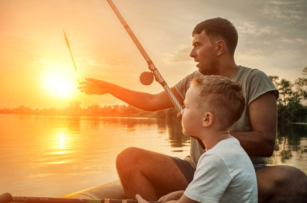 Father and sun fishing at sunrise.