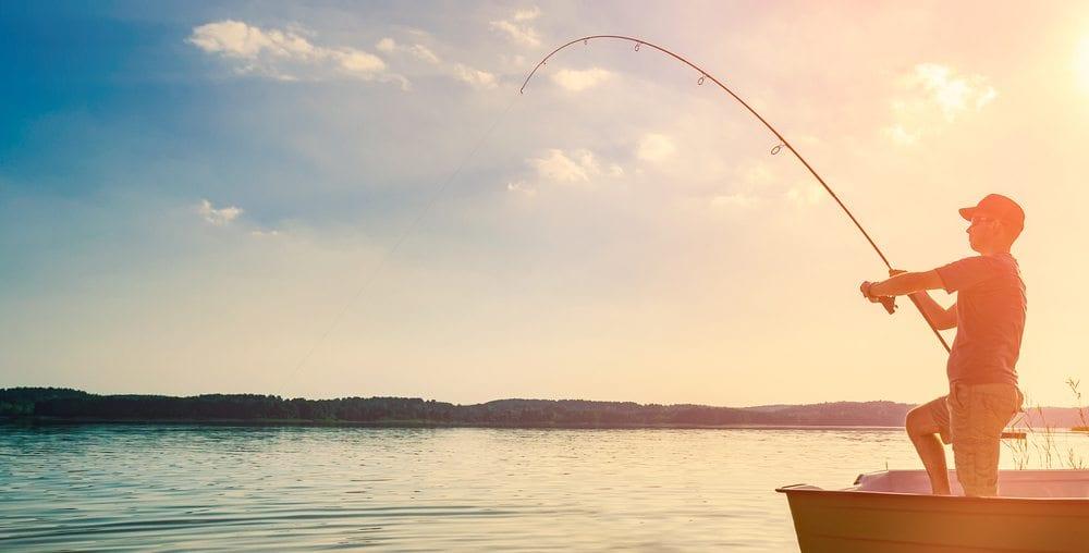 Man lake fishing in a boat.
