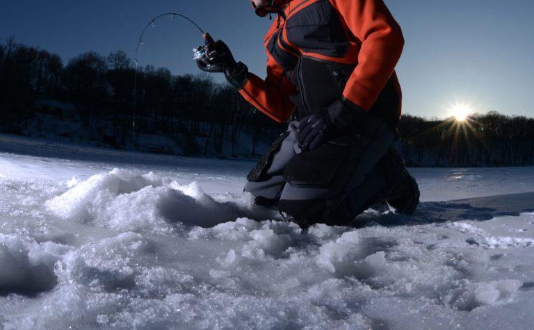 a man knelt by an ice fishing hole